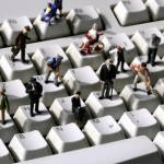 "GERMANY, Bonn, ""Online"" - Human miniatures on a computer keyboard."